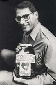 Man holding AIDS Emergency Fund penny jar.