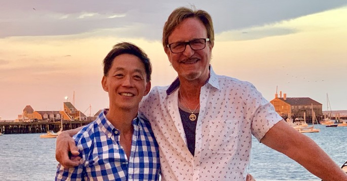 AJ Shepard and Anthony Chiu stand in front of an ocean at sunset