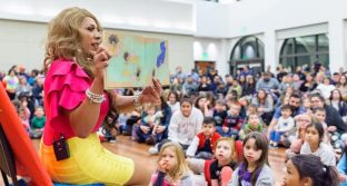 Bella Aldama reads to a crowd of children and adults