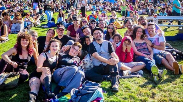 A color photograph of a group of about 20 individuals sitting together on some grass at Dolores Park in San Francisco during the Trans March of 2018. There are info booth tents and a crowd of people roaming in the background.