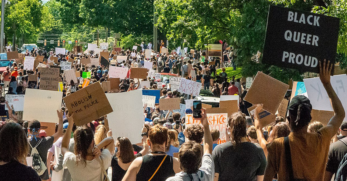 """Crowd of people at a racial-justice protest; one sign reads, """"Black Queer Proud"""""""